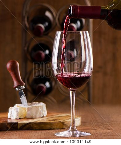 Red Wine Pouring Into Wine Glass On A Wooden Background.