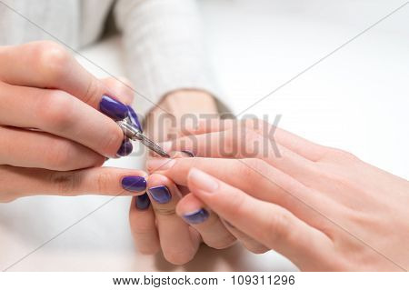 Manicurist removing cuticle from ring finger girl