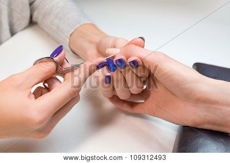 Beautician work with nail scissors at spa salon