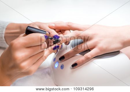 Manicurist applies nail gel polish middle finger