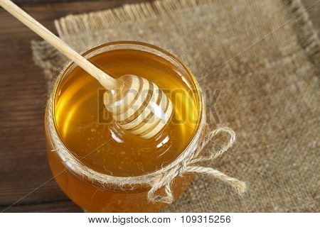 Golden honey with honeystick on wooden table.