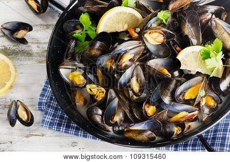 Copper Pot Of Gourmet Mussels Served On A Napkin Garnished With Lemon Slices.