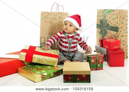 An adorable baby looking a bit overwhelmed by the assortment of wrapped gifts surrounding him.  On a white background.