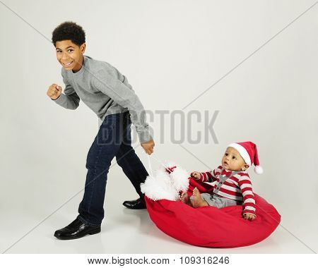 A handsome African American boy happily pulling his baby brother along the floor on Santa's sack.  On a gray background.