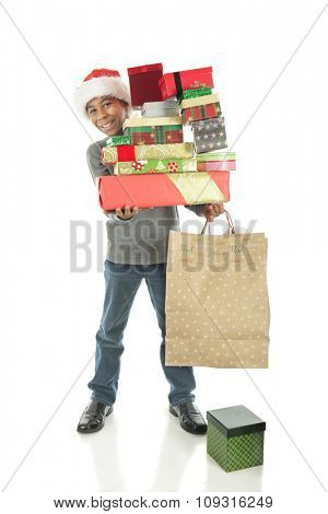 A handsome elementary boy delightedly carrying a large stack of wrapped Christmas gifts.  On a white background.