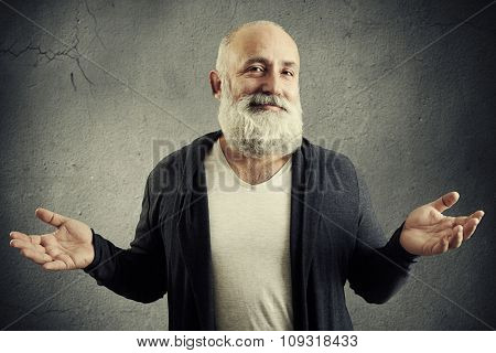 smiling good-natured man looking into the camera and waved his hands over grey wall