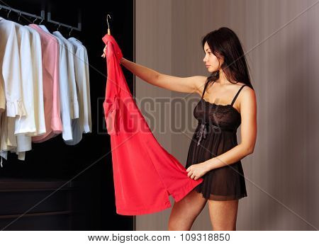 beautiful woman fits on a red dress in the shopping mall