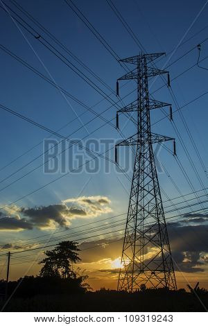 High voltage pole Transmission line tower with sunset.