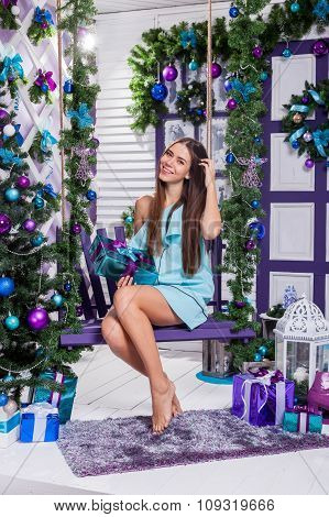 Beautiful Brunette Sitting On A Swing In A Turquoise Dress Among Christmas Toys And Gifts Near The C