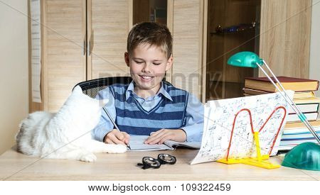 Happy boy doing homework with cat and books on table. Education concept.