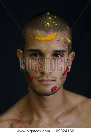 Handsome young man with skin all painted with Holi colors