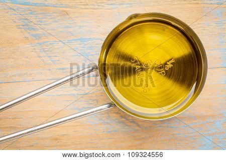 olive oil in a metal measuring cup against painted wood
