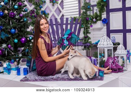 Leggy Brunette In A Burgundy Dress Sitting On A Purple Rug On The Terrace Surrounded By A Christmas
