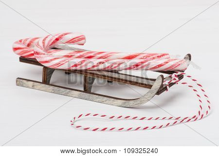 Christmas Candy Cane On Wooden Sledge. White Painted Wood Backgr
