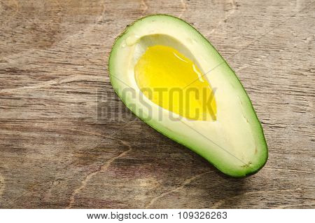 Fresh Half Avocado Like A Bowl For Oil On Wooden Background