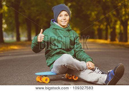 Smiling boy sitting on color plastic penny board or skateboards outdoor and showing thumbs up