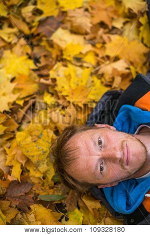 Closeup portrait of a young man lying on fallen autumn leaves.