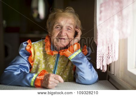 An elderly woman in Cossack clothes, a portrait by the window.