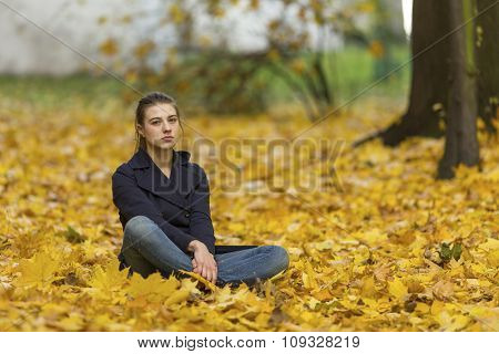 Young girl sitting on fallen leaves in autumn Park.