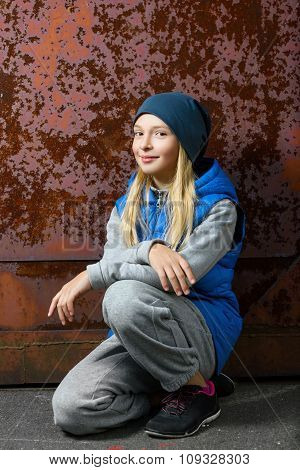 Hipster girl sitting on floor against red rusty wall