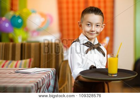 Happy cute little boy smiling waiter holding a tray width juice