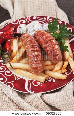 Grilled german sausages with roasted peppers and french fries