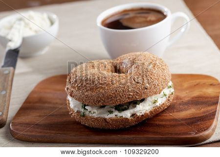 Bagel sandwich with cream cheese and parsley on a wooden cutting board