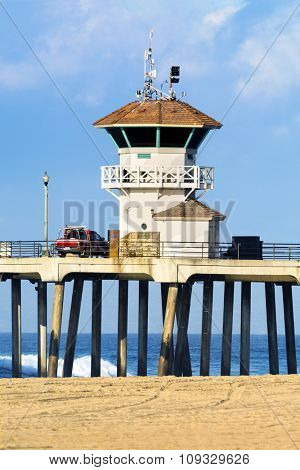 Huntington Beach watchtower on the historic pier during a bright, sunny day.