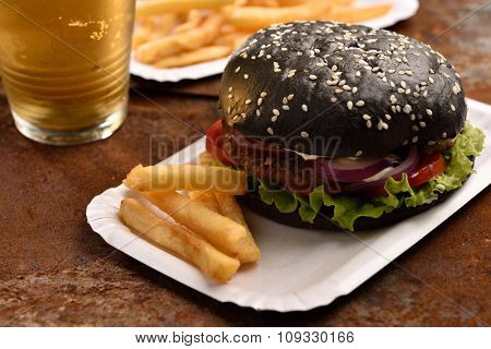 Black burger with French fries and beer