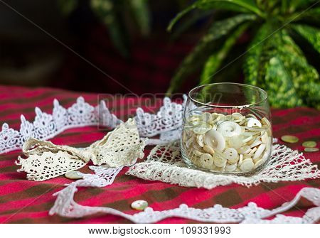 Set Of White Buttons In A Glass