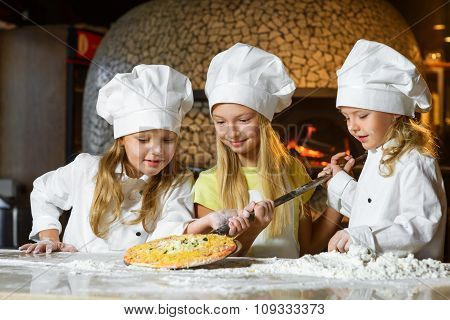 cute smiling girl chef admiring look at pizza