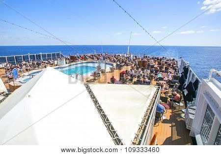 Tourists Relax And Take A Sun Bath On The Upper Deck Of A Cruise Ship