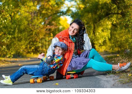 Smiling woman and boy sitting on color plastic penny boards or skateboards outdoor