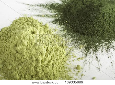Spirulina and barley grass raw powder on white background - heap.