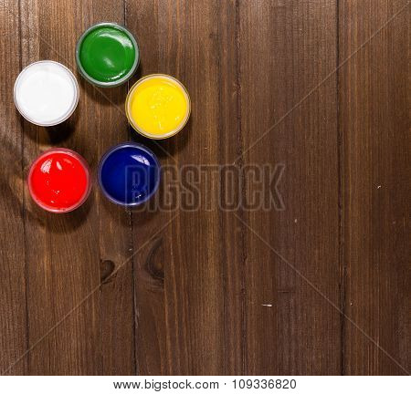 Five Jars With Multi-colored Paints Stand On A Wooden Table, The Top View