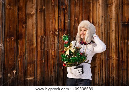 Woman With Christmas Tree Near Rustic Wall Looking Copy Space