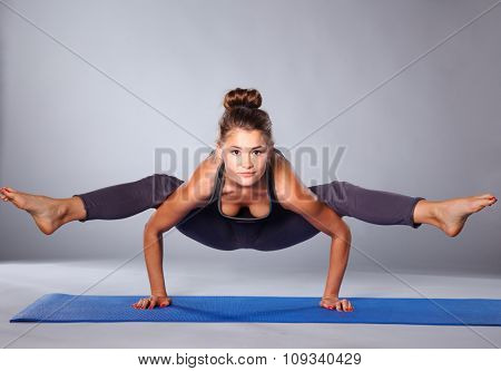 Young woman doing yoga exercise on gray background
