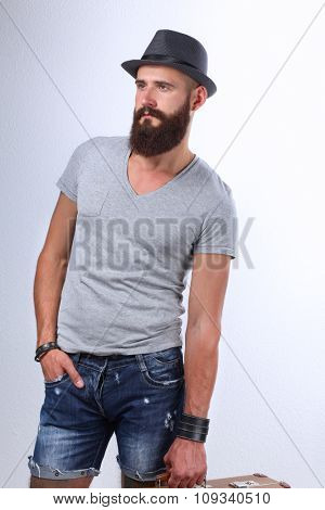 Portrait of handsome bearded man in hat standing with bad, isolated on white background