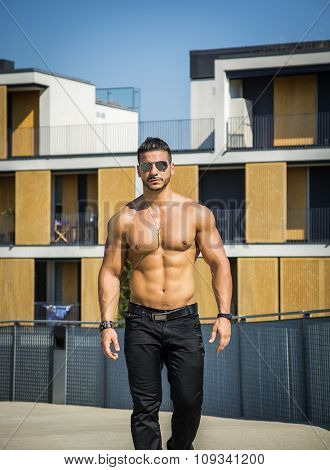 Attractive bodybuilder shirtless outdoor showing torso muscles, abs, pecs and arms, looking at camera