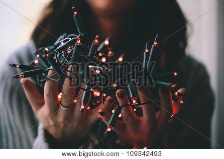 Girl holding a Christmas lamp garland.