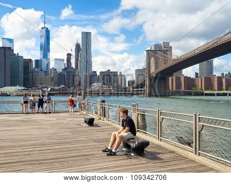 NEW YORK,USA - AUGUST 20,2015 : People at a pier in Brooklyn with the Lower Manhattan skyline and the Brooklyn Bridge on the background