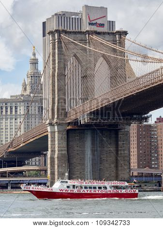 NEW YORK,USA - AUGUST 20,2015 : Sightseeing tour boat sailing under the Brooklyn Bridge in New York City