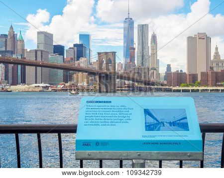 NEW YORK,USA - AUGUST 20,2015 : Sign at the Brooklyn Bridge Park telling the history of the Brooklyn Bridge with the Manhattan skyline on the background