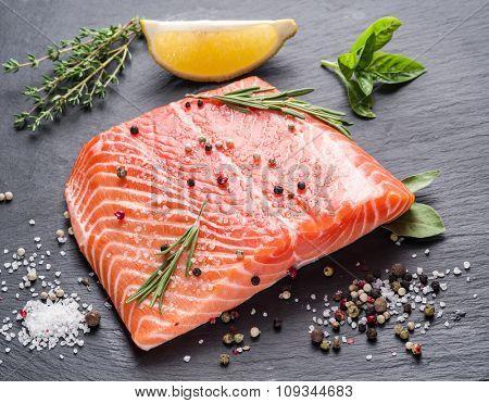 Fresh salmon on the black cutting board.
