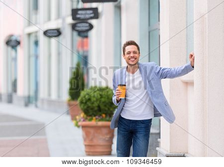 Young man with coffee outdoors