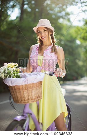 Smiling girl on a bicycle outdoors