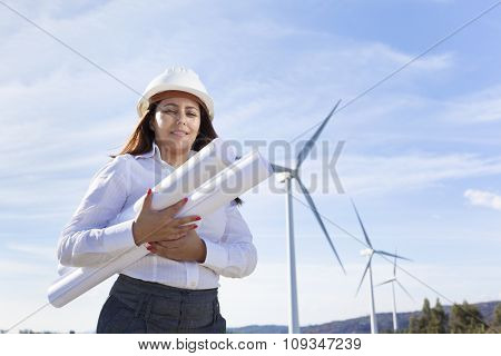 Environmental engineer holding blueprints at wind farm