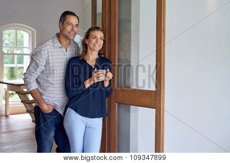Mature Caucasian smiling couple standing at terrace door enjoying a weekend coffee break
