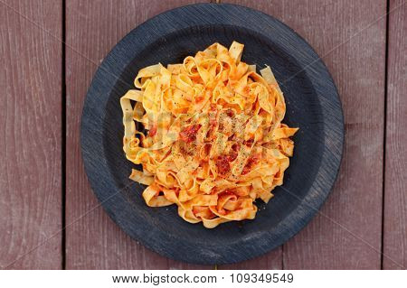 Tagliatelle with tomato sauce in wooden plate shot from above