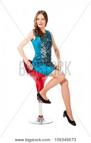 Young slim pretty woman in blue dress with sequins posing on bar chair isolated on white background